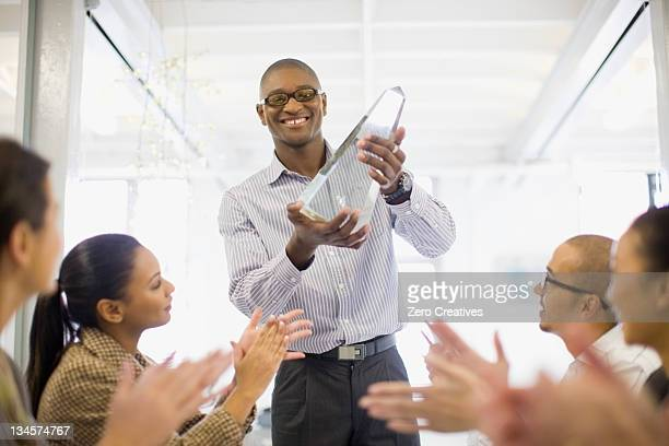 Businessman holding award in meeting