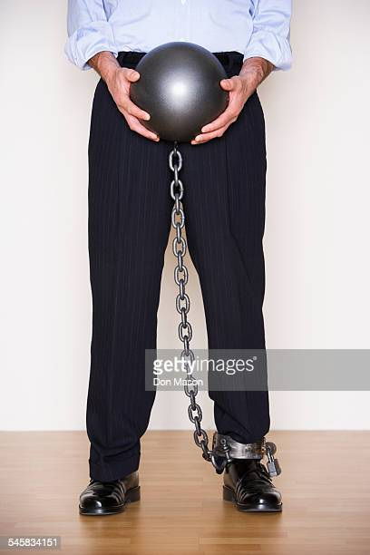 Businessman Holding Ball and Chain