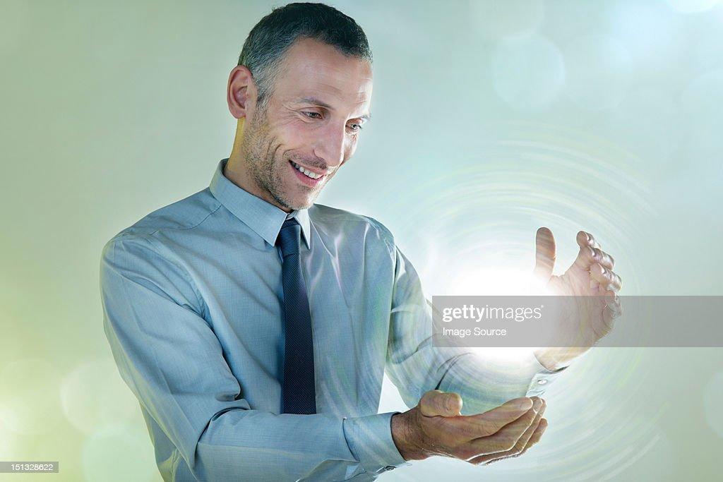 Businessman holding ball of light : Stock Photo