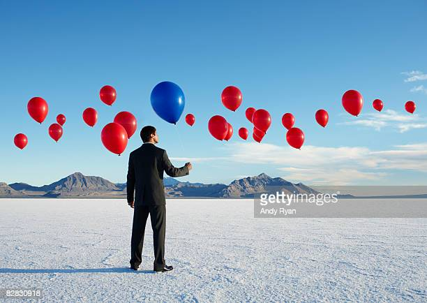 Businessman Holding Balloon in Field of Balloons