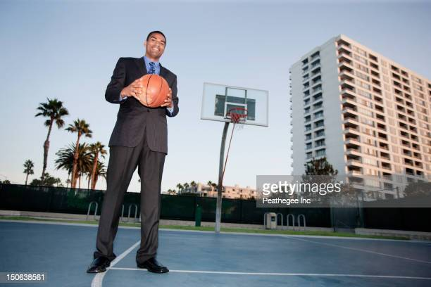 businessman holding basketball on basketball court - mid adult men stock pictures, royalty-free photos & images