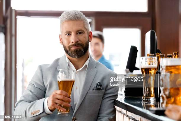 businessman holding beer glass at brewery - gray jacket stock pictures, royalty-free photos & images