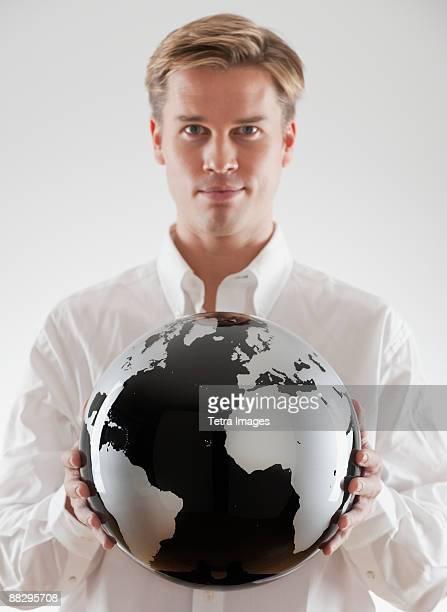 Businessman holding black and white globe
