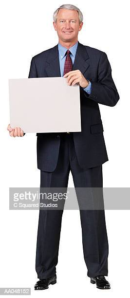 Businessman holding blank card, portrait