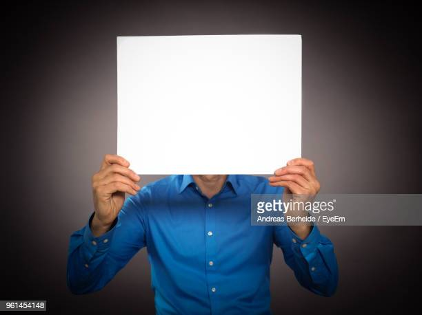 businessman holding blank placard against black background - obscured face stock pictures, royalty-free photos & images