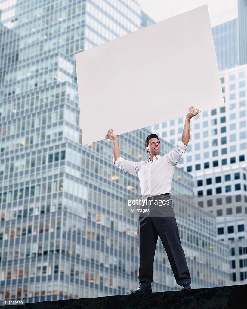 Businessman holding blank sign : Stock Photo