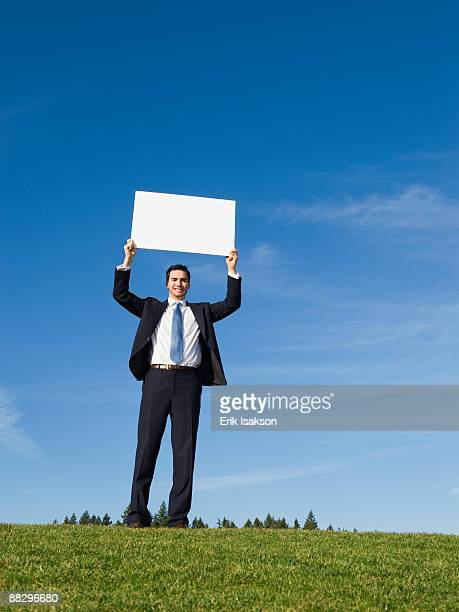 businessman holding blank sign - person holding blank sign stock pictures, royalty-free photos & images
