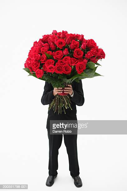 Businessman holding bouquet of red roses