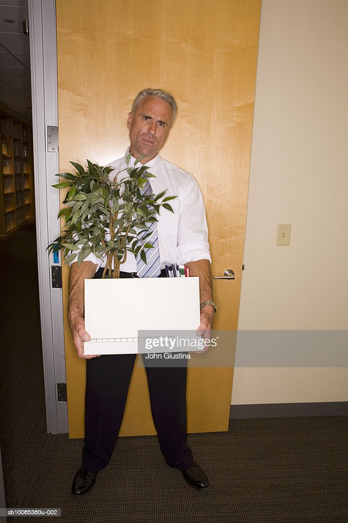 Businessman holding box and pot plant in doorway, portrait : Foto stock