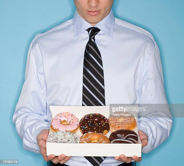 Businessman holding box of donut