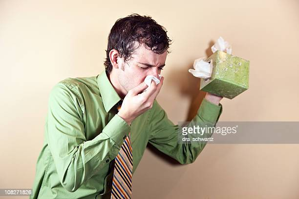 Businessman Holding Box of Tissues and Blowing Nose