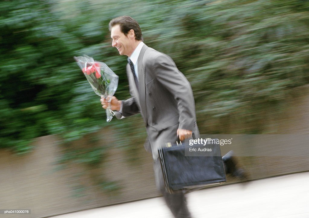 Businessman holding briefcase and bouquet of flowers, running, blurred : Stockfoto