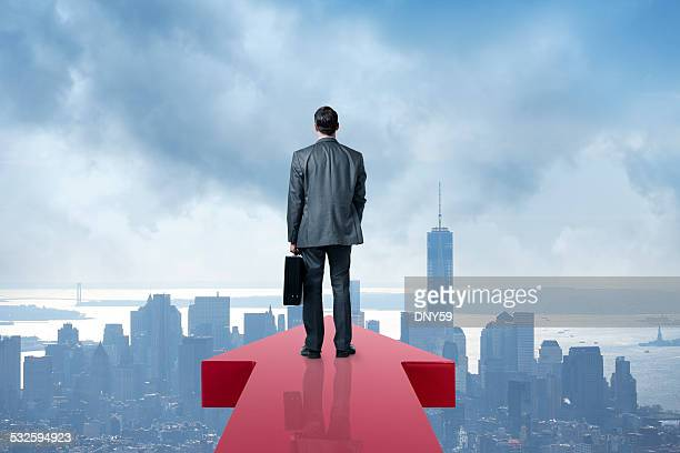 Businessman Holding Briefcase At The End Of An Arrow