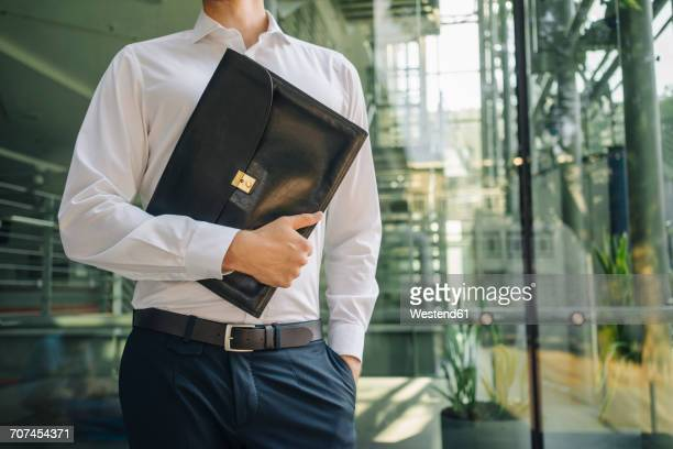 Businessman holding briefcase in lobby