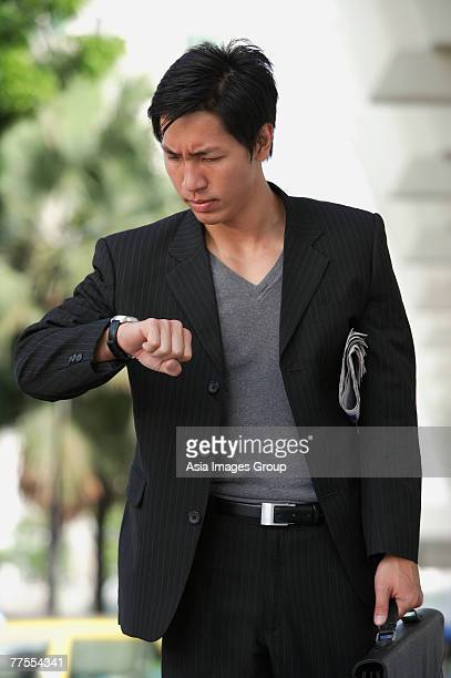 Businessman holding briefcase, looking at watch, frowning