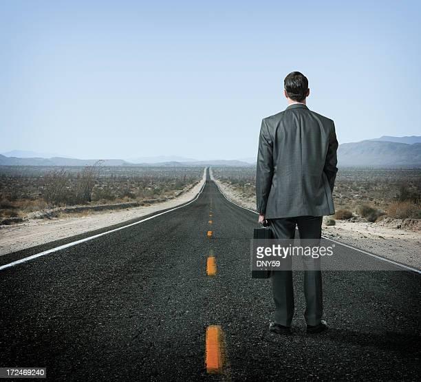 Businessman holding briefcase looking down long desert highway