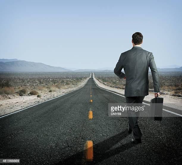Empresário segurar Pasta executiva Andar para baixo de longa Estrada no Deserto