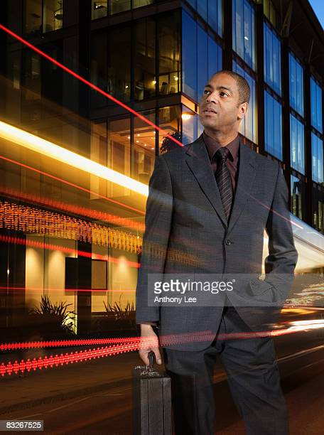 Businessman holding briefcase with light streaking around him