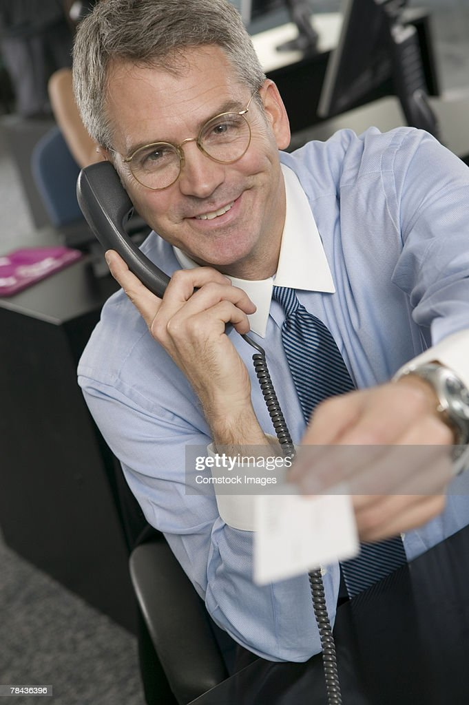 Businessman holding business card and talking on telephone : Stockfoto