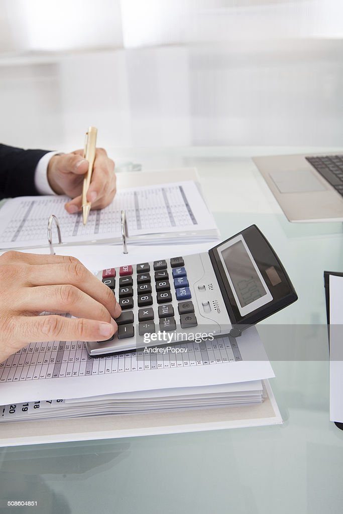 Businessman Holding Calculating Expense In Office : Stock Photo