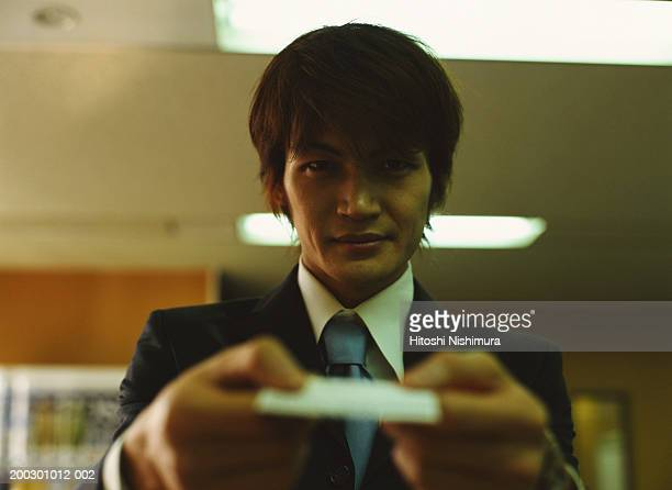 Businessman holding card, smiling