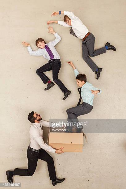 Businessman holding cardboard box while boys flying out