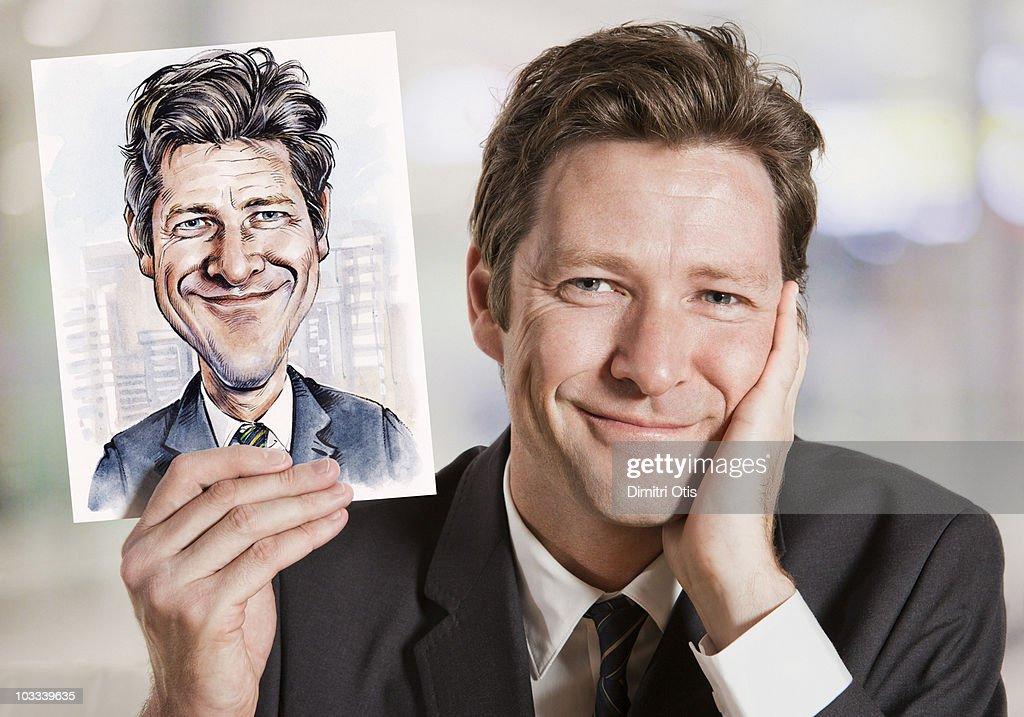 Businessman holding caricature of himself : Stock Photo