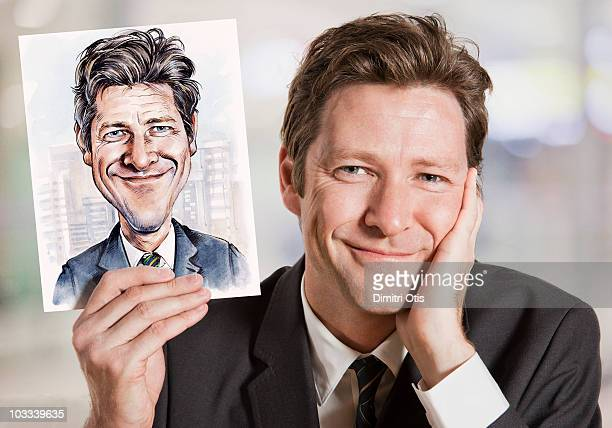 businessman holding caricature of himself - karikatuur stockfoto's en -beelden