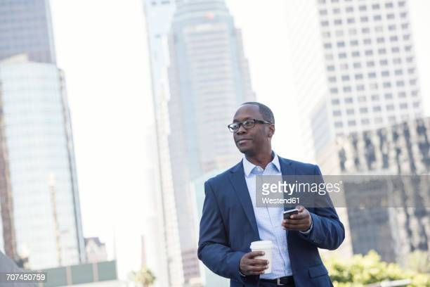 Businessman holding cell phone and takeway coffee outdoors