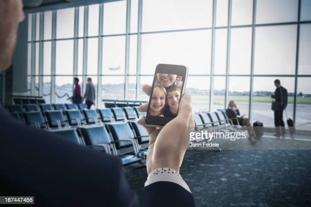 Businessman holding cell phone in airport