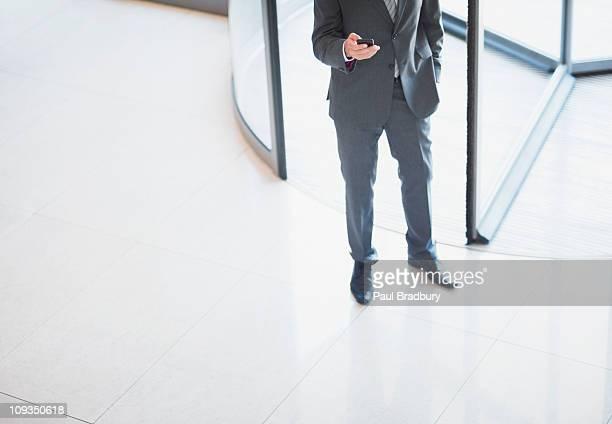 Geschäftsmann holding Handy in der Nähe einer Drehtür ausgestattet.