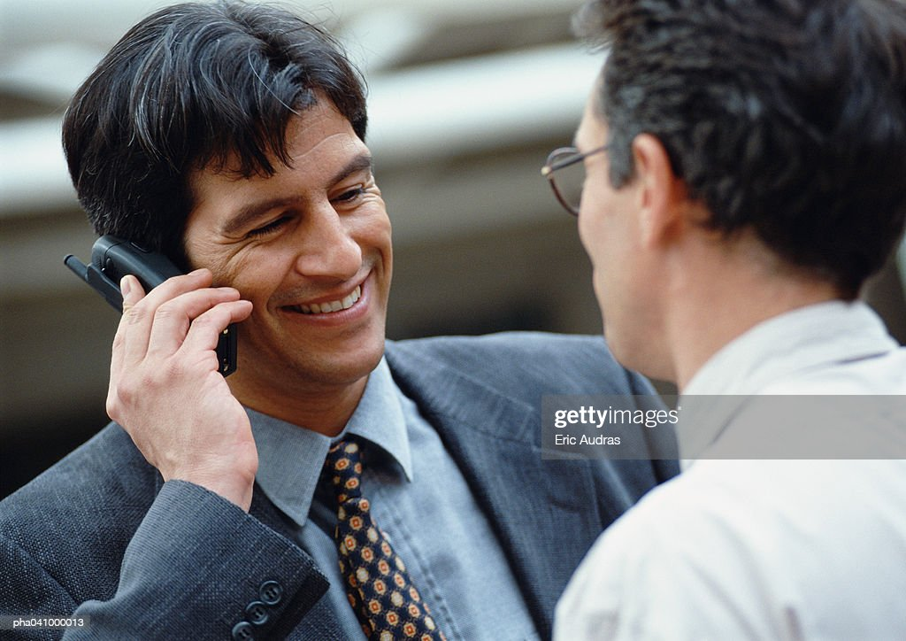 businessman holding cell phone, smiling : Stockfoto