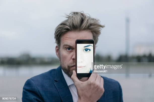 businessman holding cell phone with image of a woman in front of his eyes - illusion stock pictures, royalty-free photos & images