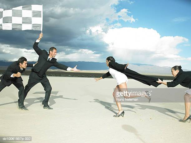 Businessman holding checkered flag and reaching out for businesswoman