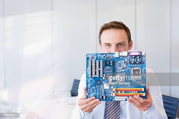 businessman holding circuit board - alleen één mid volwassen man stockfoto's en -beelden