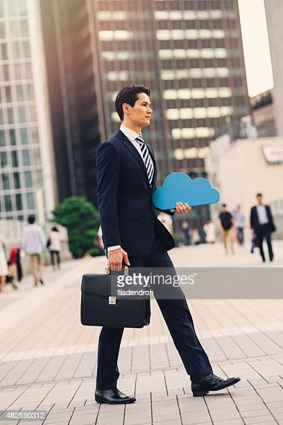 Geschäftsmann holding cloud computing-Symbol im Freien