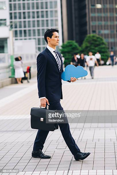 Businessman holding cloud computing icon outside