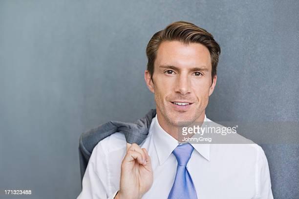 Homme d'affaires en tenant manteau sur l'épaule