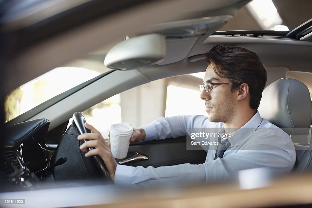 Businessman holding coffee cup and driving car : Stock Photo