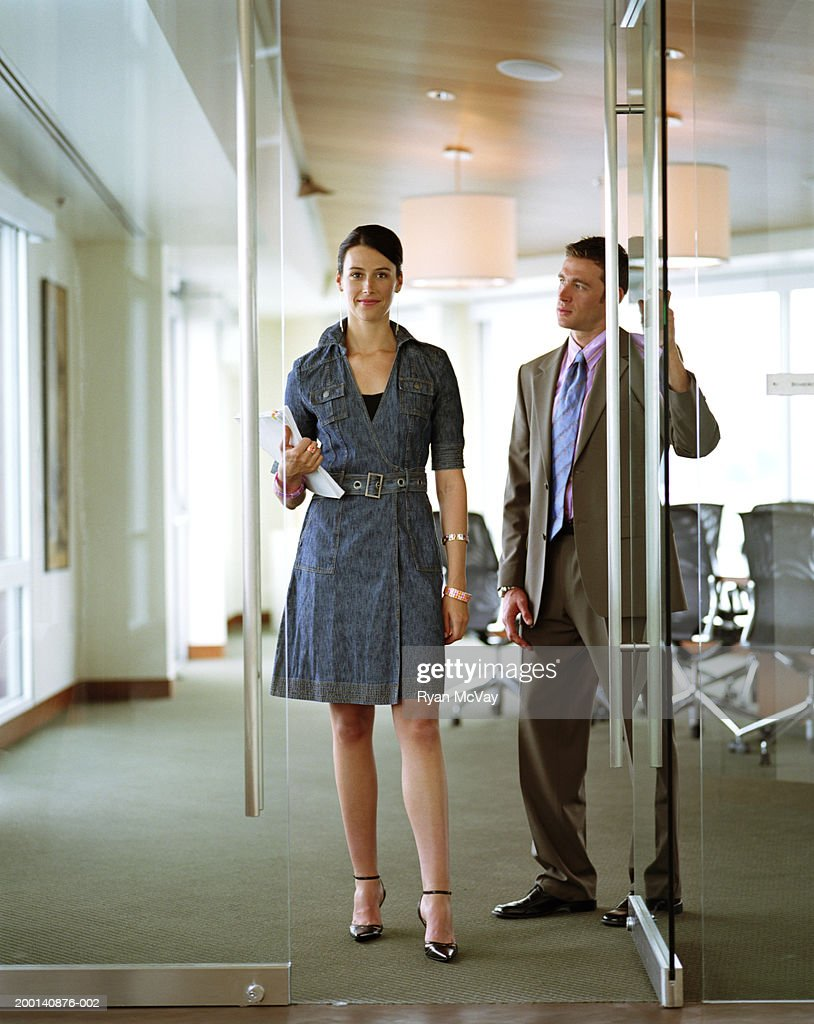 Businessman holding conference room door for businesswoman : Stock Photo