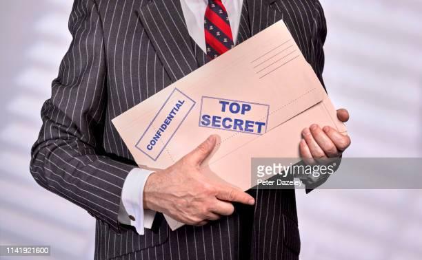 businessman holding confidential top secret folder - politica foto e immagini stock
