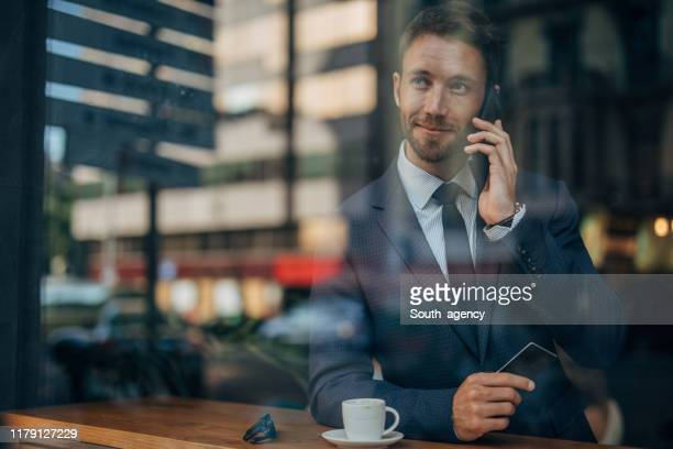 businessman holding credit card in cafe - finanças e economia imagens e fotografias de stock