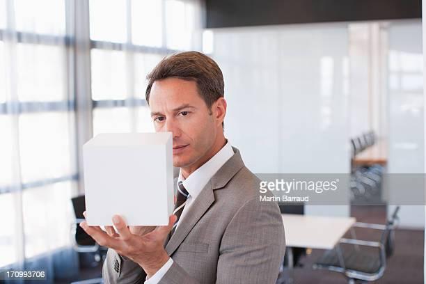 businessman holding cube in office - alleen één mid volwassen man stockfoto's en -beelden