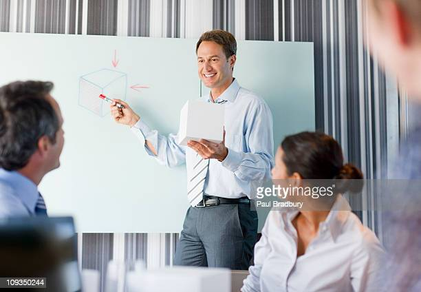 Businessman holding cube talking to co-workers in conference room