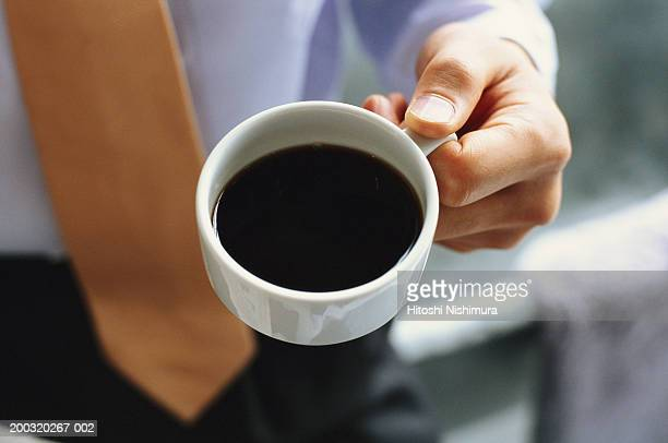 Businessman holding cup of black coffee, mid section, elevated view
