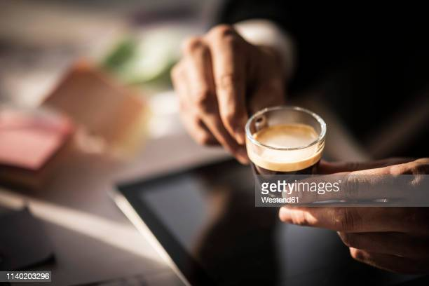businessman holding cup of coffee in his office - human body part stock-fotos und bilder