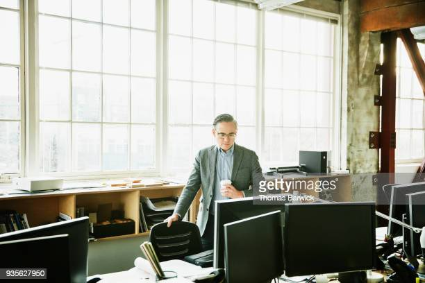 Businessman holding cup of coffee while standing at office workstation looking at computer