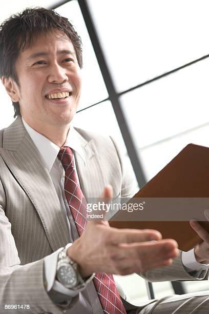 Businessman holding diary, extending hand