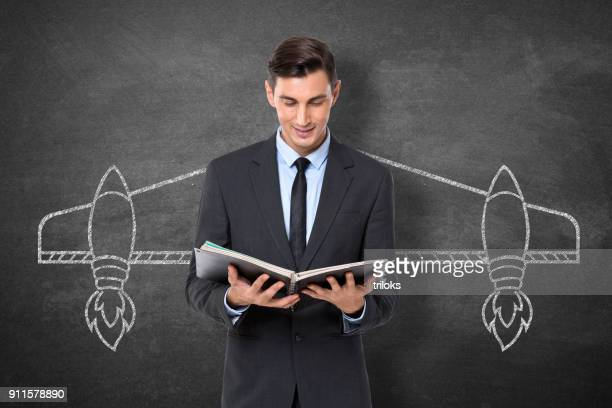 Businessman holding diary in front blackboard
