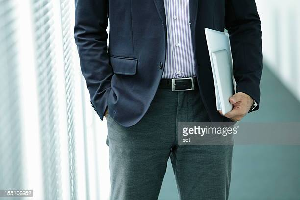 Businessman holding digital tablet and folder